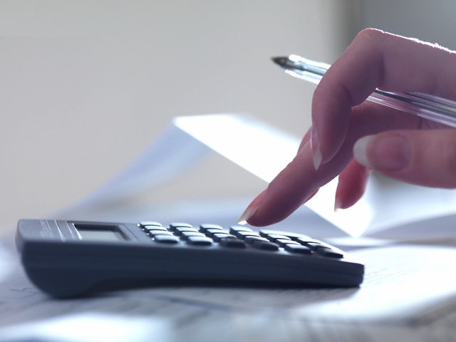 Woman holding a pen and using a calculator