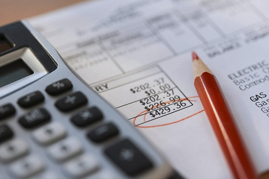 Calculator and pencil with bills